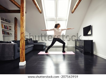 Full length image of fit woman standing on exercise mat with arms outstretched doing yoga in loving room. Caucasian female model exercising at home. - stock photo