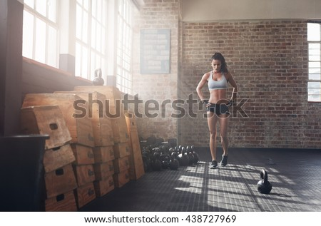 Full length image of fit young woman walking in the crossfit gym. Female athlete preparing herself before a intense training. - stock photo