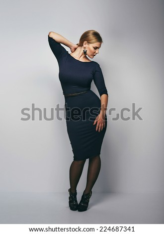 Full length image of gorgeous young woman posing in black dress. Elegant caucasian female model on grey background. - stock photo