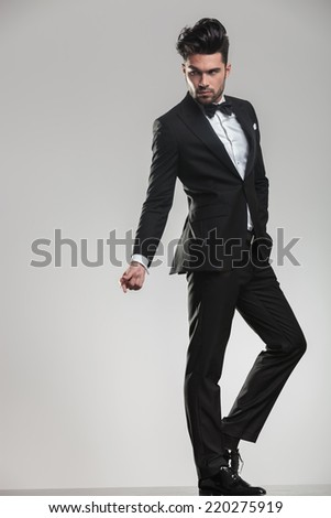 Full length image of on elegant young man snapping his finger while looking away from the camera. - stock photo