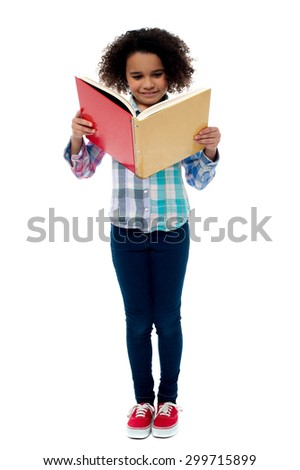 Full length image of school girl reading a book  - stock photo