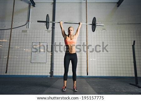 Full length image of strong young woman with barbell and weight plates overhead doing crossfit exercise. Fit female athlete lifting heavy weights. - stock photo