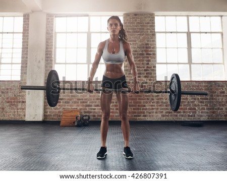 Full length image of tough young woman exercising with barbell. Determined female athlete lifting heavy weights. - stock photo
