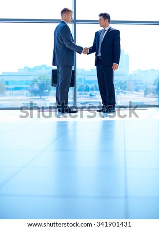 Full length image of two successful business men shaking hands with each other - stock photo