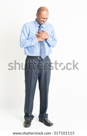 Full length Indian business man heartache, pressing on chest with painful expression, on plain background
