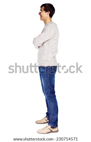 Full length left side view portrait of smiling young man in glasses and beige sweater with crossed arms on his chest isolated on white background - stock photo