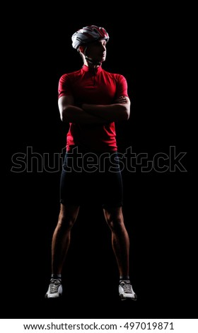 Full length low key silhouette portrait of a cyclist in a black studio
