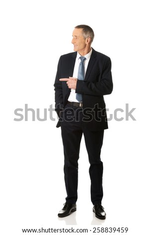 Full length mature businessman pointing to the left. - stock photo