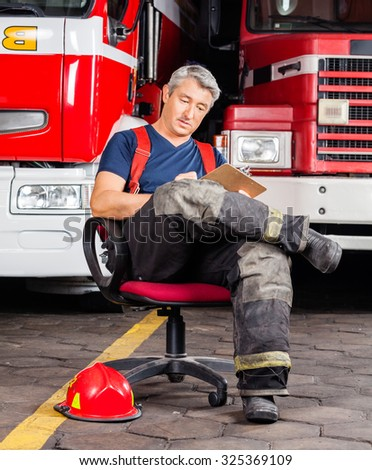 Full length mature fireman writing on clipboard while sitting against trucks at fire station - stock photo
