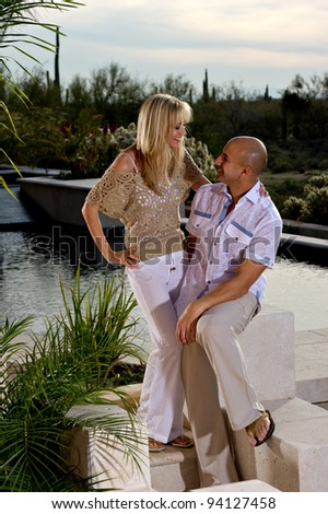 Full length of a beautiful happy couple posing next to a pool.   A green winter desert landscape is in the background. - stock photo