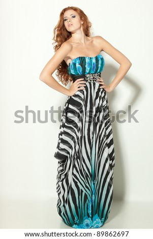 Full length of a beautiful redheaded fashion model posing in long chiffon dress