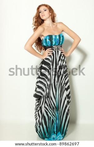 Full length of a beautiful redheaded fashion model posing in long chiffon dress - stock photo
