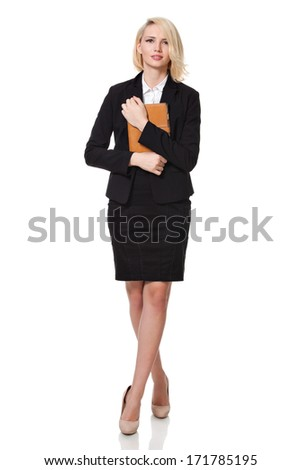 full length of a beautiful young blonde woman standing and smiling and holding a notebook  close to her chest - stock photo