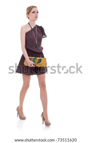 Full length of a beautiful young lady in dress walking on a white background - stock photo