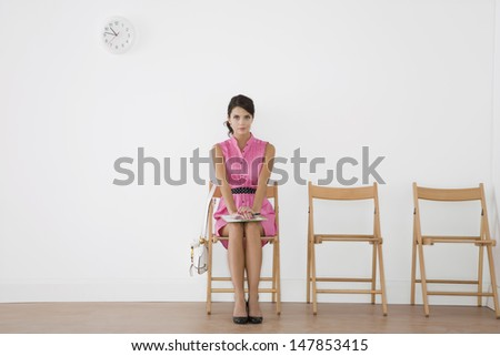 Full length of a beautiful young woman in pink dress sitting at waiting room - stock photo