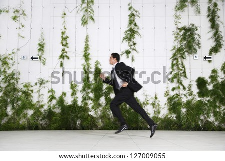 Full length of a businessman running in front of a wall with creepers - stock photo