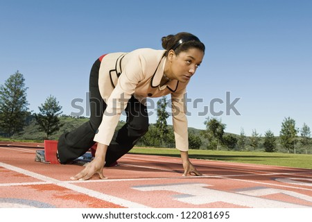 Full length of a businesswoman about to run on racing track - stock photo
