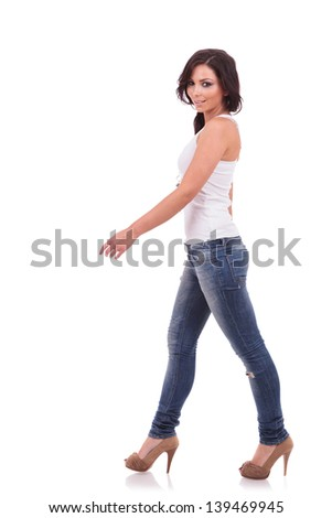 full length of a casual young woman walking to the side and looking at the camera with a smile. on white background