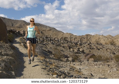 Full length of a Caucasian woman jogging on walkway - stock photo