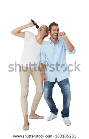 Full length of a cheerful couple singing into microphones over white background - stock photo