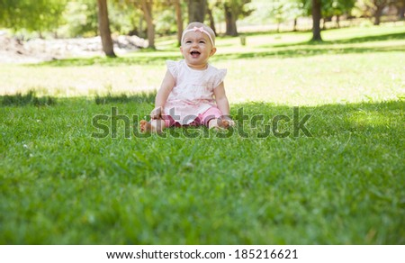 Full length of a cheerful cute baby sitting on grass at the park - stock photo