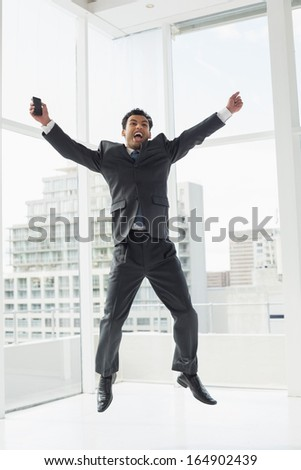 Full length of a cheerful elegant young businessman cheering in a bright office - stock photo