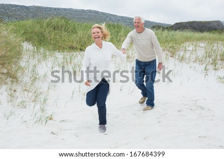 Full length of a cheerful senior couple running at the beach - stock photo