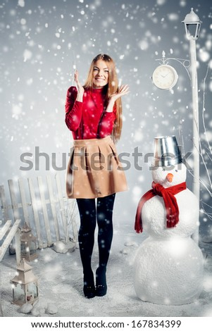 Full length of a cheerful young woman by snowman in winter studio interior - stock photo