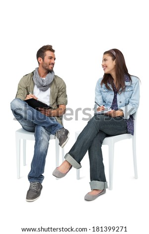 Full length of a cool young couple writing in notepads over white background - stock photo