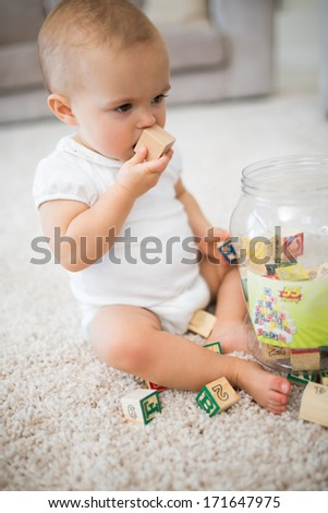 Full length of a cute little baby with toys sitting on carpet at home - stock photo