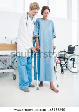 Full length of a doctor helping patient in crutches at the hospital - stock photo
