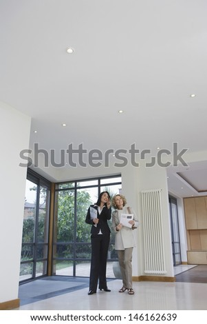 Full length of a female real estate agent and woman observing new property - stock photo