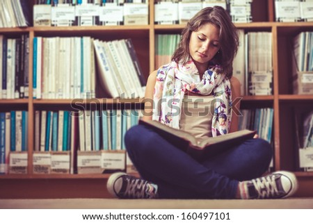 Full length of a female student sitting against bookshelf and reading a book on the library floor - stock photo