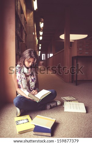 Full length of a female student sitting and reading a book in the library aisle - stock photo
