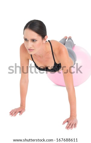 Full length of a fit young woman doing push ups on fitness ball over white background - stock photo