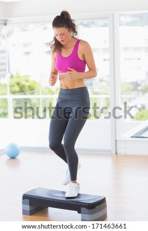 Full length of a fit young woman performing step aerobics exercise in gym - stock photo
