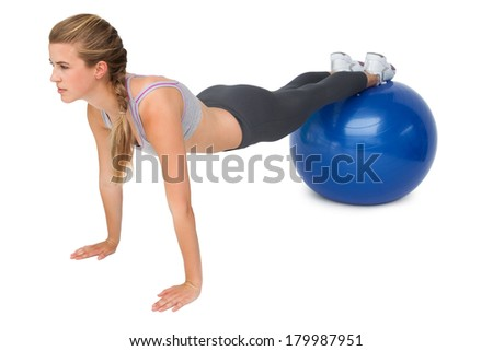 Full length of a fit young woman stretching on fitness ball over white background - stock photo