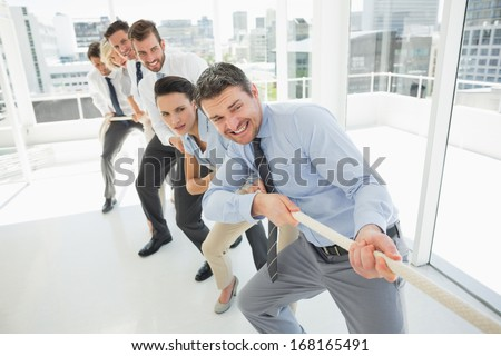 Full length of a group of business people pulling rope in a bright office - stock photo