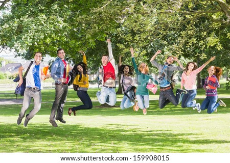 Full length of a group of college students jumping in the park - stock photo