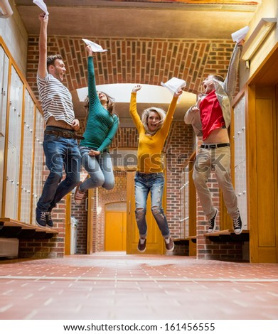 Full length of a group of students jumping in college corridor - stock photo