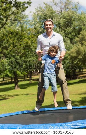 Full length of a happy boy and father jumping high on trampoline in the park - stock photo