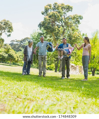Full length of a happy extended family walking in the park - stock photo