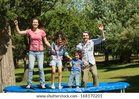 Full length of a happy family jumping high on trampoline in the park - stock photo