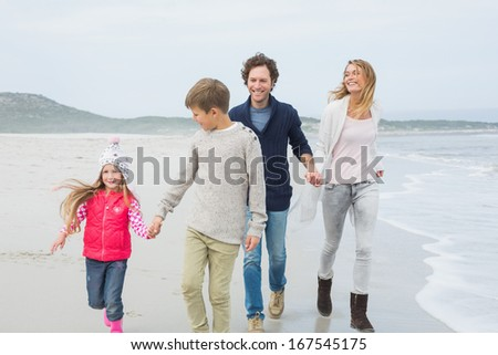 Full length of a happy family of four walking on sand at the beach - stock photo