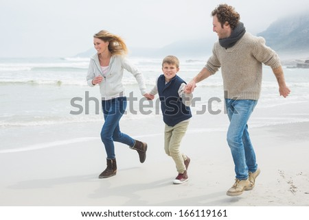 Full length of a happy family of three running on sand at the beach - stock photo