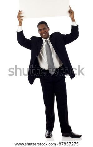 Full length of a happy young black businessman holding blank sign above his head - copyspace isolated over white background - stock photo
