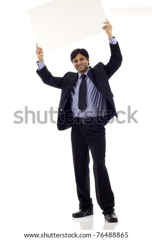 Full length of a happy young Indian businessman holding blank sign above his head - copyspace isolated over white background - stock photo