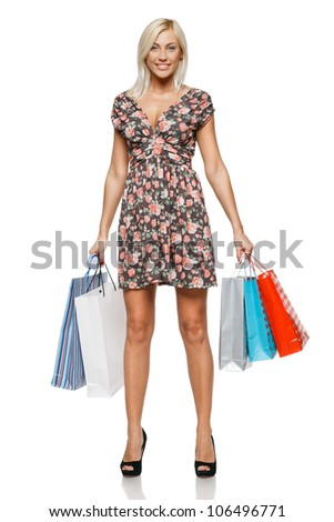 Full length of a happy young woman holding shopping bags over white background