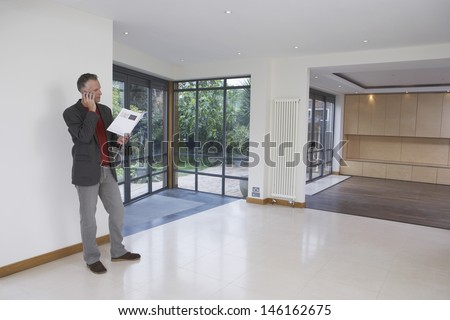 Full length of a male real estate agent using mobile phone in new property - stock photo