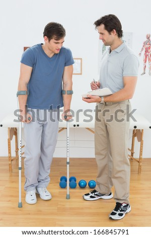 Full length of a male therapist discussing reports with a disabled patient in the gym at hospital - stock photo
